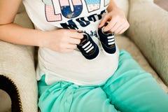 Schwangere Frau, die kleine Babyschuhe hält Stockbild