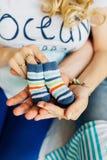 Schwangere Frau, die kleine Babyschuhe hält Lizenzfreie Stockbilder