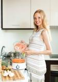 Schwangere Frau, die Lachsfische kocht Stockbilder