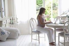Schwangere Frau, die Laptop im Wohnzimmer verwendet Lizenzfreies Stockfoto