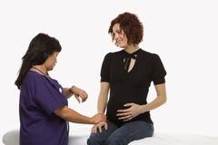 Schwangere Frau, die lebenswichtige Zeichen überprüfen lässt. Stockfotos