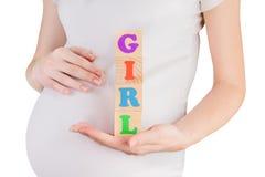 Schwangere Frau, die MÄDCHEN-Zeichen hält Lizenzfreie Stockfotos