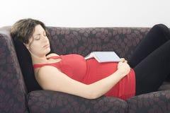 Schwangere Frau, die mit Buch auf Sofa schläft Lizenzfreie Stockfotos
