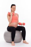 Schwangere Frau, die mit Dummköpfen ausarbeitet Lizenzfreie Stockbilder