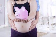 Schwangere Frau, die moneybox zeigt Stockfotografie