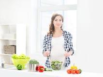 Schwangere Frau, die nährendes Lebensmittel in der Küche zubereitet Stockbild