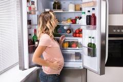 Schwangere Frau, die nach Lebensmittel sucht lizenzfreies stockbild