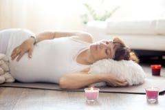Schwangere Frau, die nach Yogapraxis in Shavasana-Haltung an sich entspannt Stockfotos