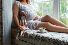 Schwangere Frau, die nahe dem Fenster sitzt Stockbild