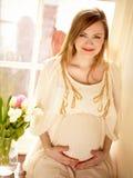Schwangere Frau, die nahe Fenster sitzt Lizenzfreie Stockfotos