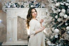 Schwangere Frau, die oben einen Weihnachtsbaum kleidet Neues Jahr Lizenzfreies Stockbild