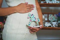 Schwangere Frau, die Pferdspielzeug nahe ihrem Bauch hält Stockfotografie