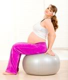 Schwangere Frau, die pilates Übungen auf Kugel tut Stockbilder