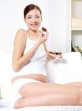 Schwangere Frau, die süße Plätzchen isst Stockfoto