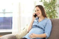 Schwangere Frau, die am Telefon spricht lizenzfreie stockfotos
