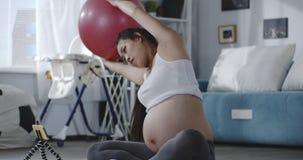 Schwangere Frau, die Tutorvideo während des Trainings aufpasst