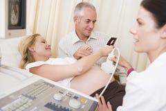 Schwangere Frau, die Ultraschall vom Doktor erhält Lizenzfreie Stockfotos