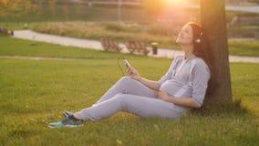 Schwangere Frau, die unter Baum hört stock video