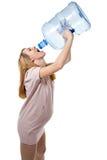 Schwangere Frau, die von der Flasche trinkt Stockbild