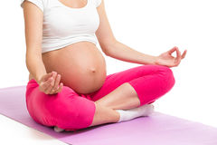 Schwangere Frau, die in Yogalotussitz sitzt Stockbild