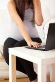 Schwangere Frau, die zu Hause arbeitet Stockbild