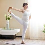Schwangere Frau, die zu Hause ausgestreckte Hand zur Yogahaltung der großen Zehe tut Lizenzfreie Stockfotografie