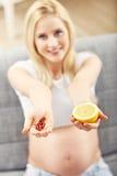 Schwangere Frau, die zu Hause Pillen und Zitrone hält stockfoto