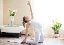 Schwangere Frau, die zu Hause ustrasana Yogahaltung tut Lizenzfreies Stockfoto