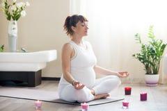 Schwangere Frau, die zu Hause während der Yogapraxis meditiert Stockfotos
