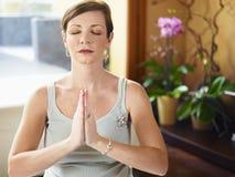 Schwangere Frau, die zu Hause Yoga tut Stockbild