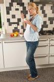 Schwangere Frau, die zu Mittag isst Stockbilder