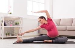Schwangere Frau, die zuhause ausbilden ausdehnt stockbilder