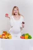 Schwangere Frau, die zwischen Apfel und Schokolade wählt Stockbild