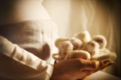 Schwangere Frau hält Babyschuhe an Stockfoto