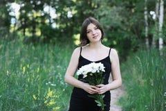 Schwangere Frau hält weiße Blumen und untersucht die Kamera Stockfotografie