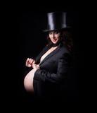 Schwangere Frau im Abendkleid und im Hutzylinder Stockfoto