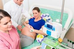 Schwangere Frau im Arbeitsraum mit Doktor und Krankenschwester Lizenzfreie Stockbilder
