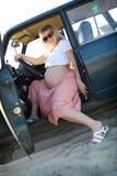 Schwangere Frau im Auto Stockbilder