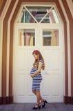 Schwangere Frau im gestreiften Kleid, das draußen aufwirft lizenzfreies stockbild