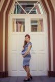 Schwangere Frau im gestreiften Kleid, das draußen aufwirft stockbilder