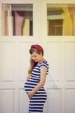 Schwangere Frau im gestreiften Kleid, das draußen aufwirft lizenzfreie stockfotos