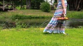 Schwangere Frau im Kleiderweg auf Flussufer mit Frucht im Korb stock video footage