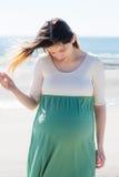 Schwangere Frau im Knickentenkleiderhaar, das im Wind auf dem bea durchbrennt Lizenzfreies Stockbild