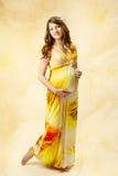 Schwangere Frau im langen Kleid über gelbem Kunsthintergrund. Stockfoto