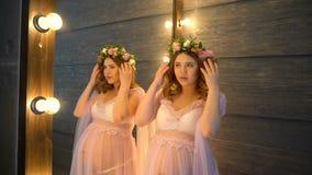 Schwangere Frau im rosa peignoir steht nahen Spiegel Sie setzte Hand auf ihren Bauch stock footage