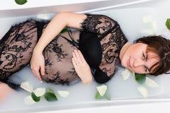 Schwangere Frau im sexy Spitzekleid, das im Bad mit den Blumenblättern sich entspannt stockfotos