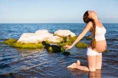 Schwangere Frau im Sport-BH, der Übung im Entspannung auf Yogahaltung auf Meer tut Stockfoto