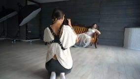Schwangere Frau im weißen peignoir auf Fotosession stock video