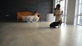 Schwangere Frau im weißen peignoir auf Fotosession Fotoaufnahme stock video footage