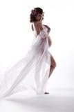 Schwangere Frau im weißen wellenartig bewegenden Flugwesenkleid. Lizenzfreies Stockbild